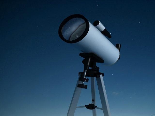 Telescope set up outdoors at dusk