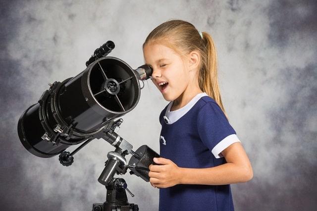 Child looking into telescope