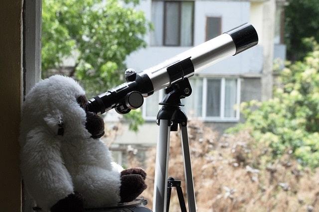 Telescope set up in window with a stuffed monkey