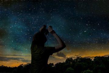 Silhouette of a man stargazing with binoculars